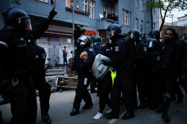 Police officers detain a demonstrator during a May Day rally in Berlin