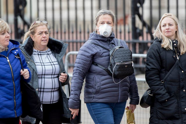 A woman wearing a protective face mask walks past Buckingham Palace