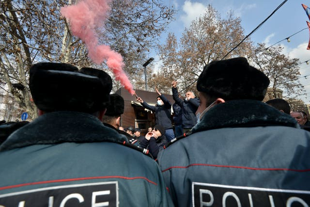 Police block opposition demonstrators letting off flares