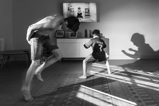 A photo issued by Historic England from its Picturing Lockdown Collection by Francesca Brecciaroli showing children taking part in the Joe Wicks PE sessions in the living room of their home in Beckenham, south London