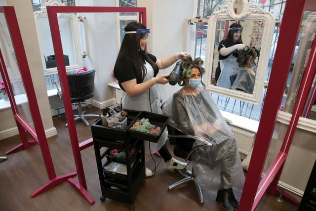 Salon manager Gemma Inglis works on the hair of Shireen Inglis at The Lunatic Fringe in Glasgow as they demonstrate some of the changes put in place to help protect against coronavirus. Hairdressers across Scotland are preparing to reopen to customers on Wednesday as lockdown measure are eased
