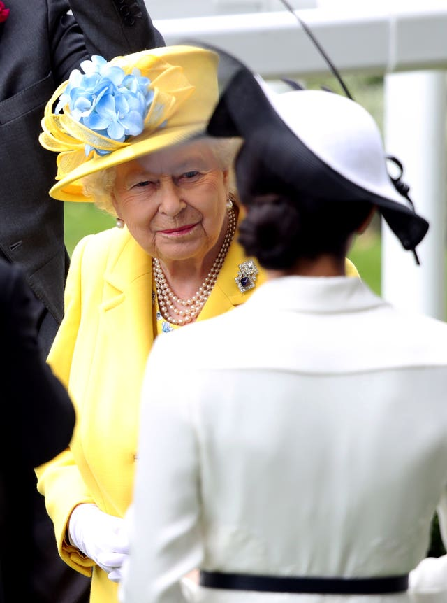 Queen Elizabeth II and the Duchess of Sussex during day one of Royal Ascot at Ascot Racecourse.