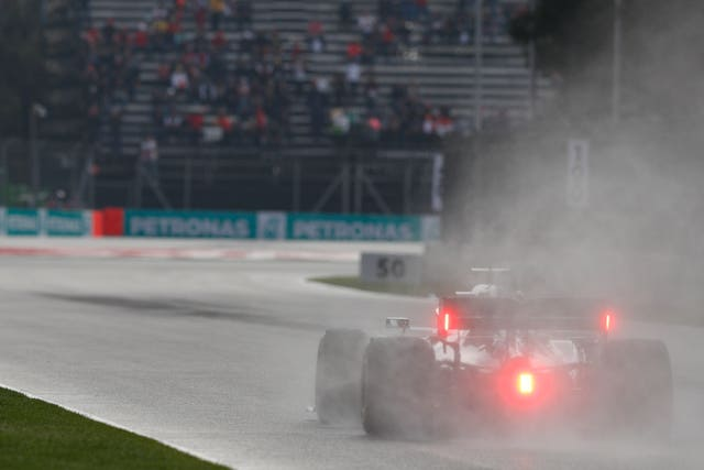Lewis Hamilton's car throws up spray on the wet track in Mexico
