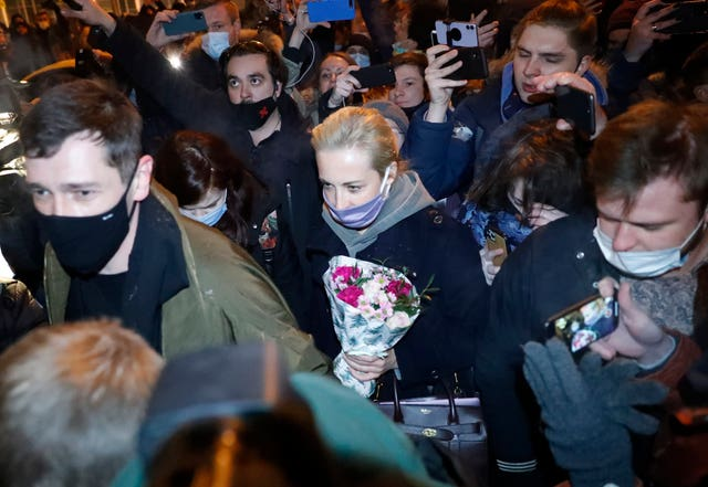Mr Navalny's wife Yulia is surrounded by people as she leaves Moscow's Sheremetyevo airport