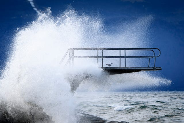 Waves hit a diving board during a storm on the shore of Lake Geneva, in Lutry, Switzerland