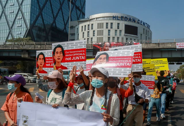 Demonstrators display pictures of detained Myanmar leader Aung San Suu Kyi during a protest against the military coup in Yangon