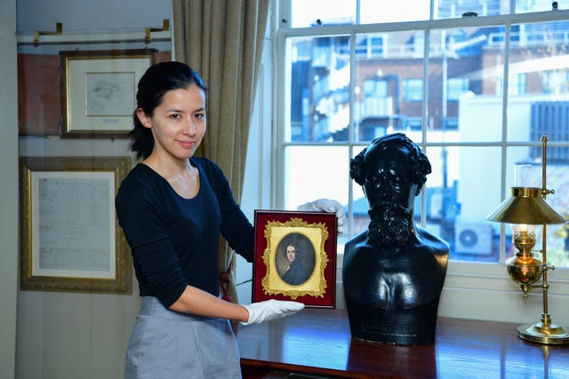 Louisa Price, curator at the Charles Dickens Museum in London, holding a portrait of the author by Margaret Gillies