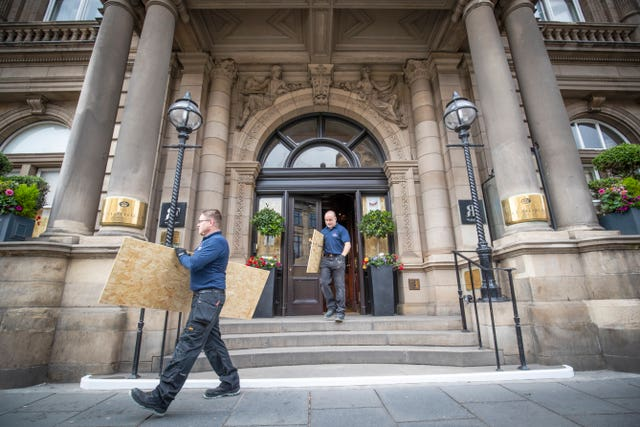 Members of the maintenance team at The Balmoral, Edinburgh, remove boards from the front door as the hotels starts to make preparations for re-opening next month as Scotland prepares for the lifting of further coronavirus lockdown restrictions