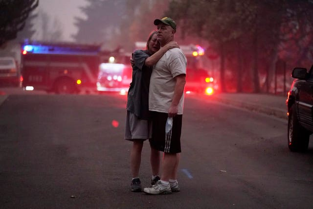 A couple, who declined to give their names, embrace while touring in an area devastated by fire in Oregon