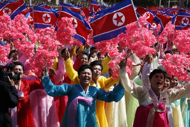 Participants cheer as they take part in a parade for the 70th anniversary of North Korea