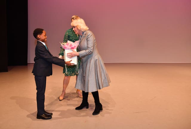 The Duchess of Cornwall receives a bouquet of flowers from a pupil on stage during a visit to Elmhurst Ballet School in Birmingham