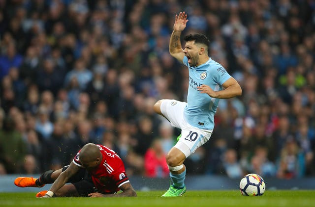 Sergio Aguero and Manchester United's Ashley Young battle for the ball