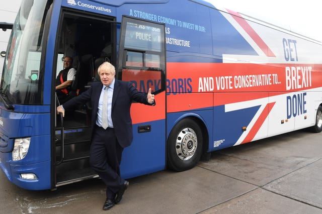 Boris Johnson by the Conservative Party battle bus in Middleton, Greater Manchester (Stefan Rousseau/PA)