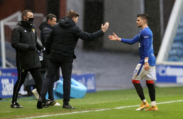 Hagi high-fives Rangers manager Steven Gerrard as he is substituted