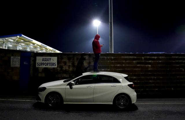 A fan stands on top of a car to watch Barrow's FA Cup first round tie with AFC Wimbledon at Holker Street. With most post-lockdown games taking place behind closed doors, supporters have come up with novel ways to watch their teams, including using ladders and booking hotel rooms overlooking pitches. Home fans would have been disappointed on this occasion as Barrow were eliminated on penalties.