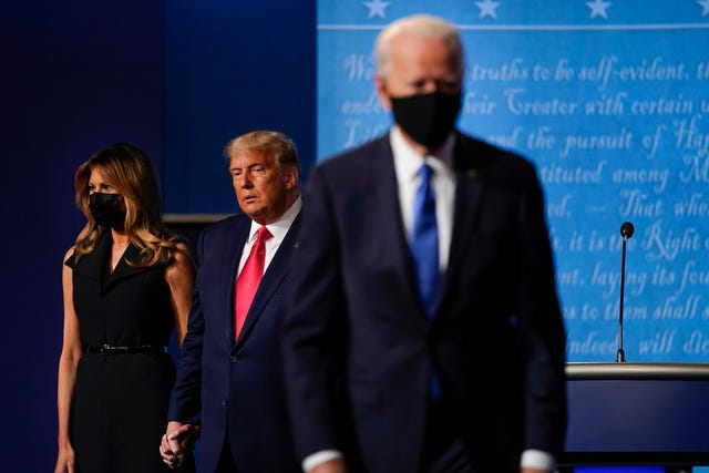 Melania Trump, left, and President Donald Trump, centre, remain on stage as Democratic presidential candidate former Vice President Joe Biden, right, walk away at the conclusion of the second and final presidential debate at Belmont University in Nashville, Tennesse (Julio Cortez/AP)