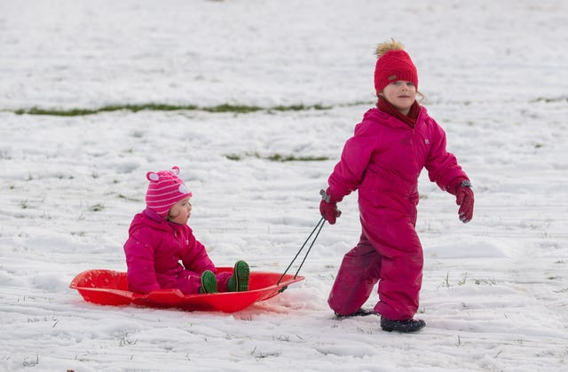 Children sledge down hill