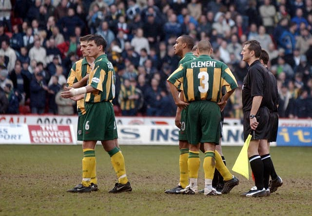 West Brom players react as referee Eddie Wolstenholme abandons the game
