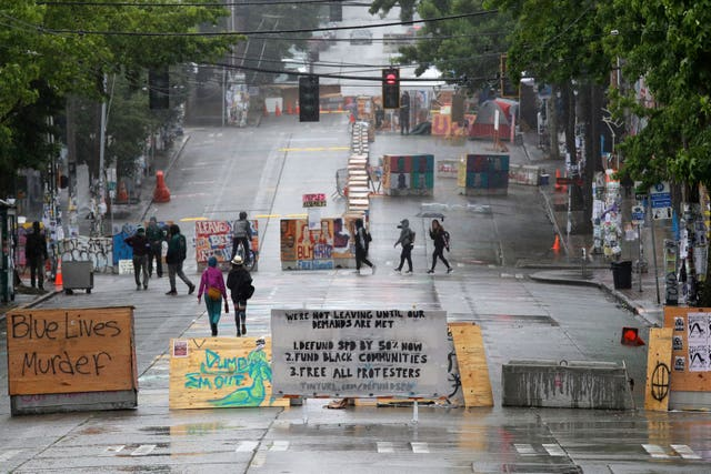 People walk past barricades in Seattle (Elaine Thompson/AP)