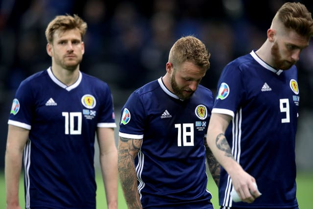 Stuart Armstrong, Johnny Russell and Oli McBurnie, l-r, react to defeat in Astana