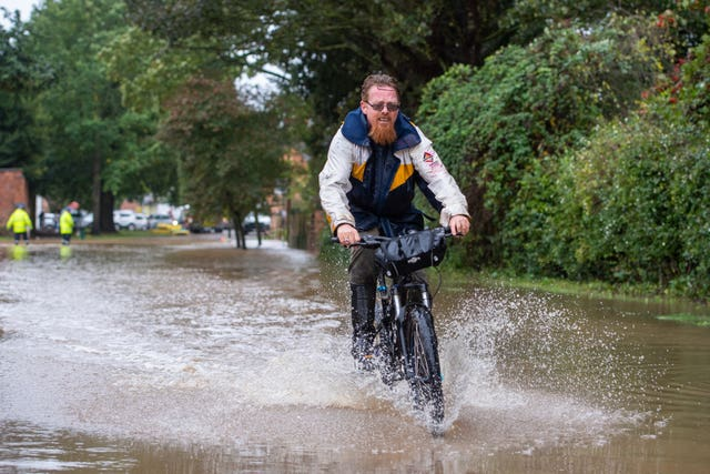 A man cycles through floodwater in Cossington, Leiceste