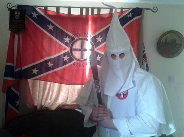 Adam Thomas wearing the hooded white robes of the Ku Klux Klan