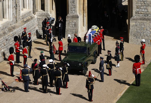 The Duke of Edinburgh's coffin, covered with Personal Standard, is carried to the purpose-built Land Rover Defender ahead of his funeral at Windsor Castle, Berkshire