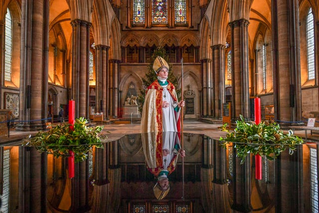 Chorister Bishop Sebastian Kunzer stands beside the baptismal font as he prepares for the Feast of St Nicholas at Salisbury Cathedral (Ben Birchall/PA)