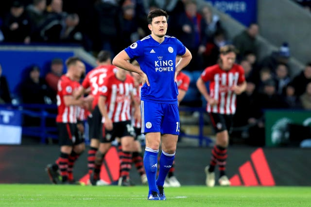 Harry Maguire appears dejected as Shane Long (back) scores Saints' second goal