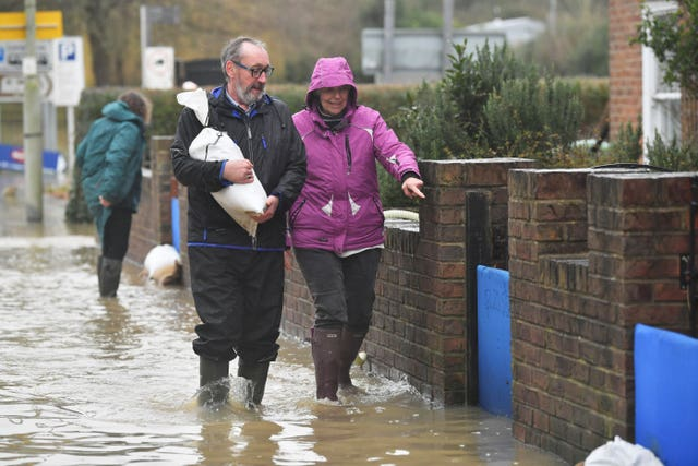 Residents of Gloucester Road in Tewkesbury collect sandbags to enforce their flood defences (Ben Birchall/PA).