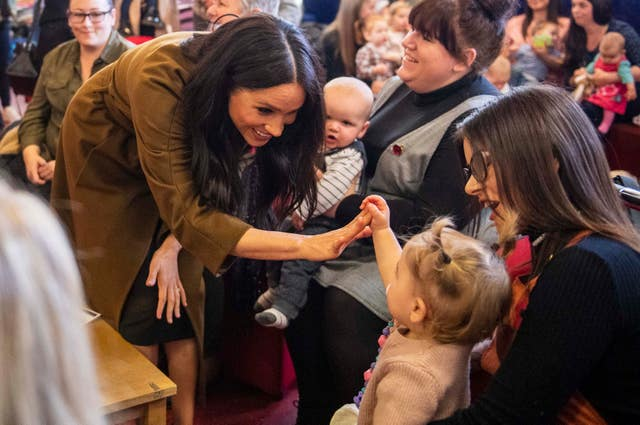 The Duchess of Sussex high fives a delighted toddler