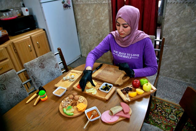Fatima Ali prepares cheese-plate takeaways at her home kitchen in Baghdad, Iraq