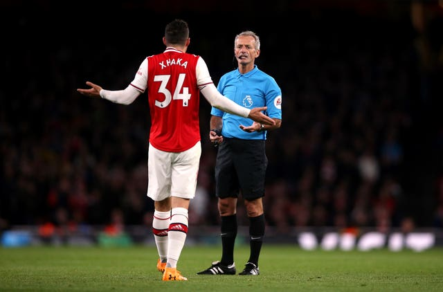 Granit Xhaka speaking to referee Martin Atkinson before his substitution