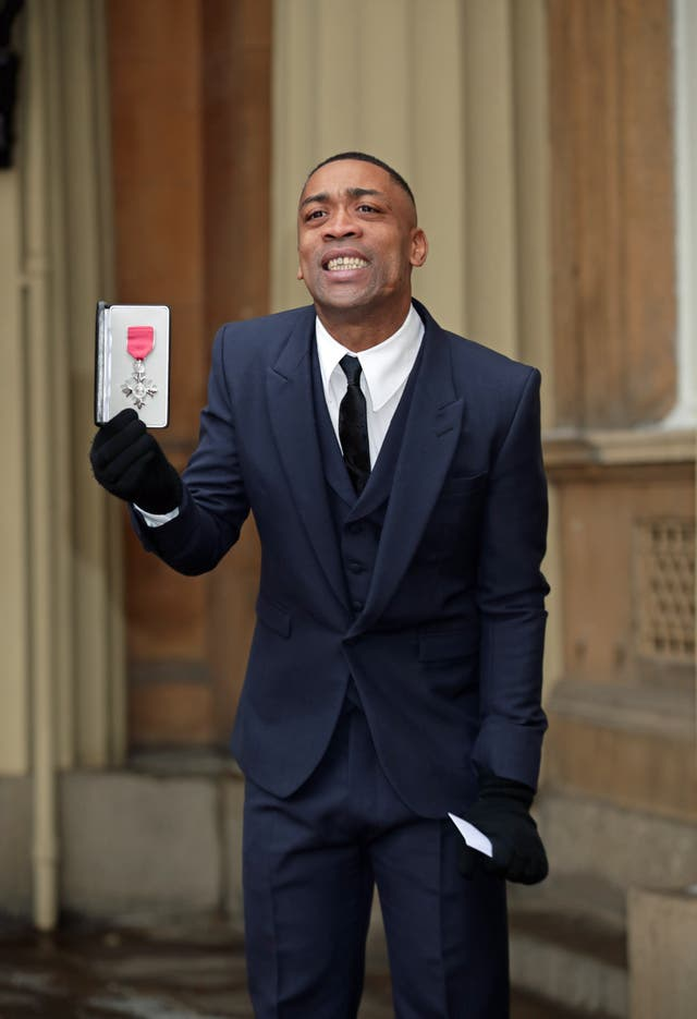 Wiley holds his MBE at Buckingham Palace.