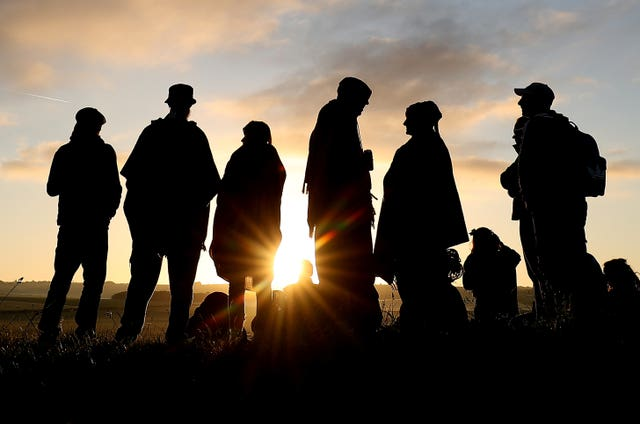 People watch the sun rise at the Avebury stone circle in Wiltshire