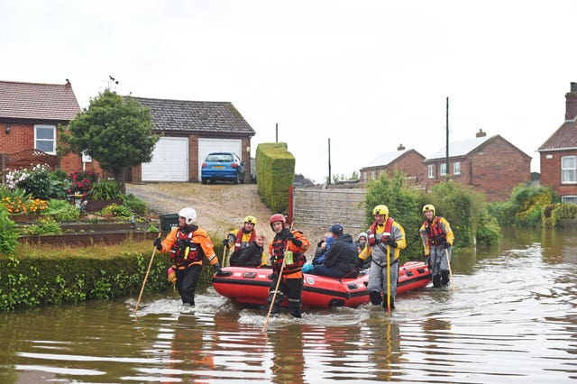 Residents are taken to safety in an inflatable boat by rescue workers in Wainfleet All Saints, in Lincolnshire, where streets and properties are flooded after the town had more than two months of rain in just two days