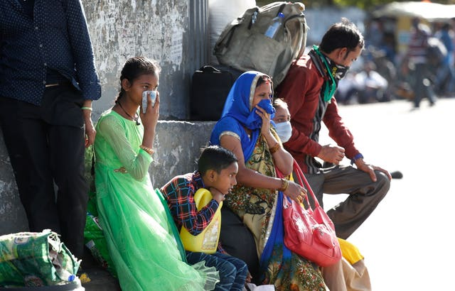 A migrant family wait for transportation to travel to their respective villages following a lockdown amid concern over the spread of coronavirus in New Delhi, India