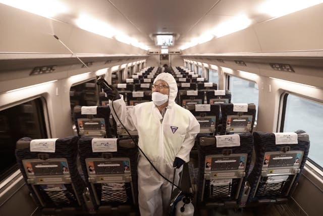 An employee sprays disinfectant on a train as a precaution against coronavirus at Suseo Station in Seoul, South Korea