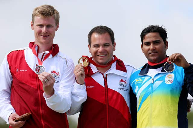 England's Steven Scott steps onto the podium to receive his gold medal following the Men's Double Trap, with silver medalist England's Matthew French (left) and bronze medalist India's Asab Mohd (right) at the 2014 Commonwealth Games