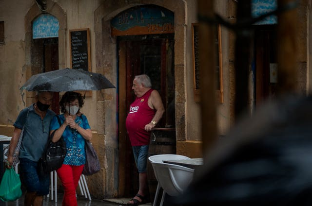 A man stands in a bar entrance as people walk by in Barcelona, Spain