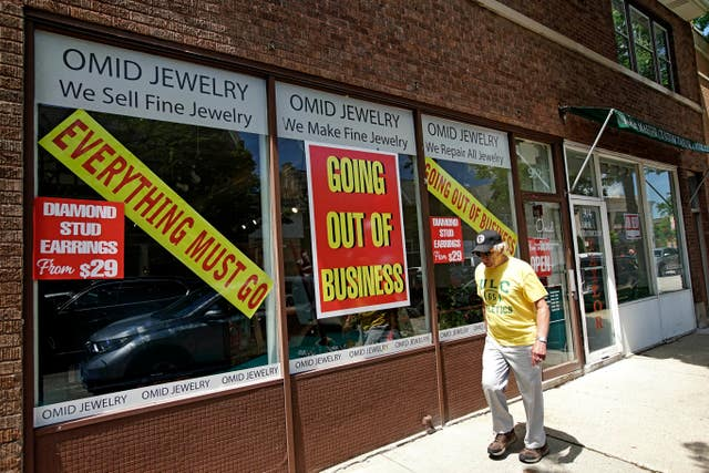 A man walks past a retail store that is going out of business due to the coronavirus pandemic in Illinois