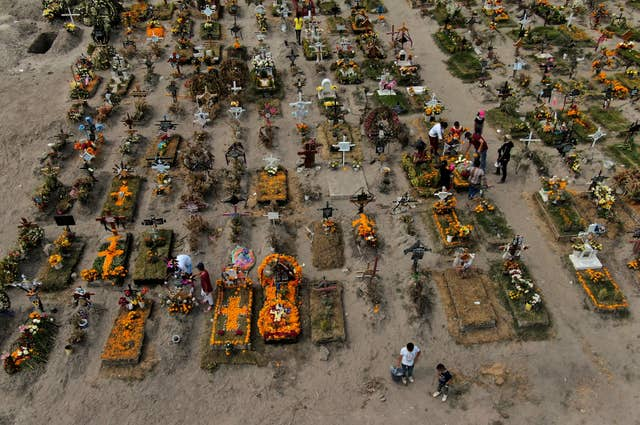 People visit the graves of their relatives buried at the Valle de Chalco municipal cemetery (Fernando Llano/AP)