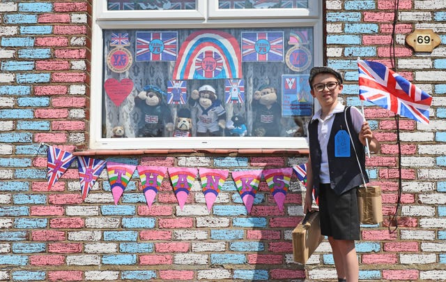 Alex Glover, 10, dressed as a Second World War evacuee outside his home in Sittingbourne, Kent, where he has created a VE Day theme which includes a tribute to 100-year-old Captain Tom Moore