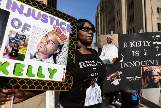 A supporter of R Kelly protests in front of the court