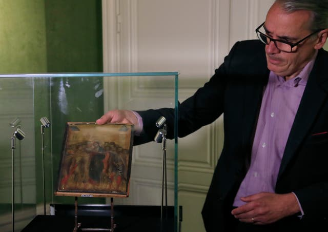 Art expert Stephane Pinta takes out of a glass case a painting by Italian master Cimabue in Paris