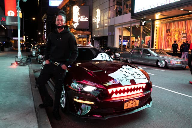 Andre Godfrey poses with his 2018 Ford Mustang EcoBoost  - with glowing red shark teeth embedded in the grill - in New York's Times Square during the coronavirus pandemic