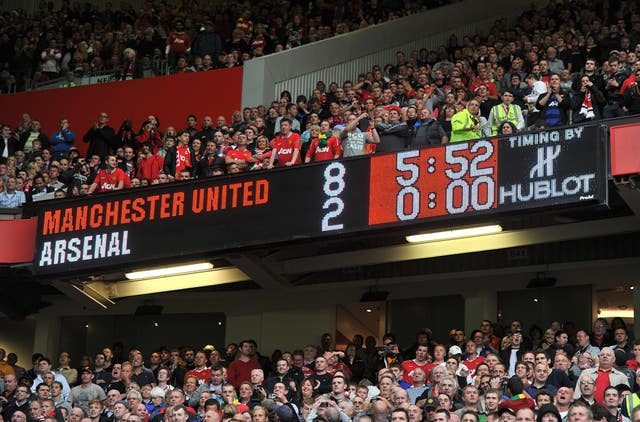 The Old Trafford scoreboard shows Manchester United 8 Arsenal 2 in 2011