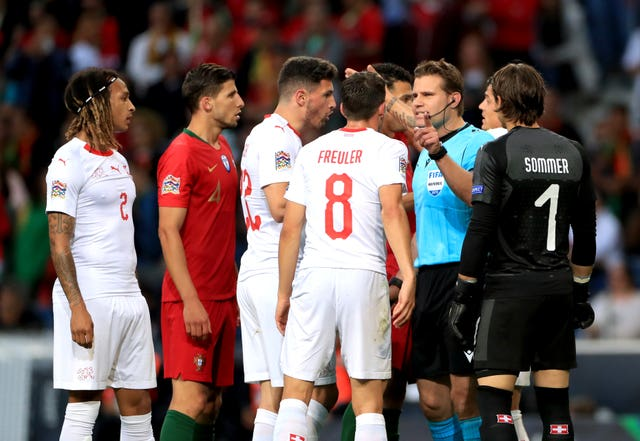 Referee Felix Brych (second right) took his time over a VAR check (PA)