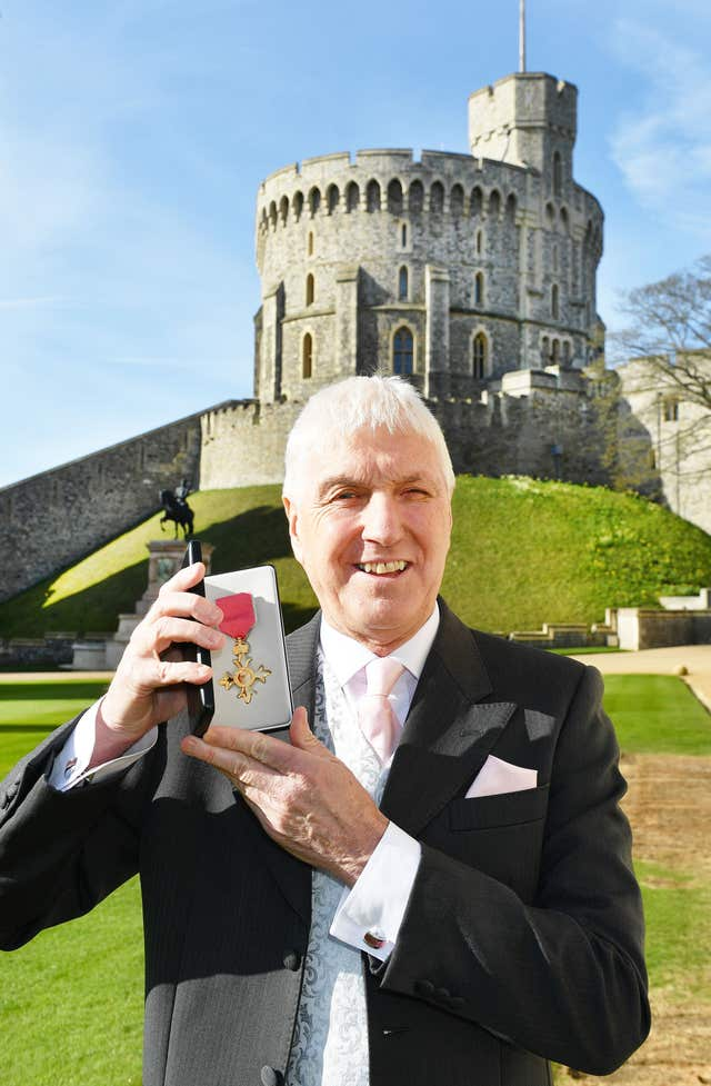 Former rugby union referee Edward Morrison holds his OBE that was presented to him by Queen Elizabeth II at an Investiture ceremony at Windsor Castle.