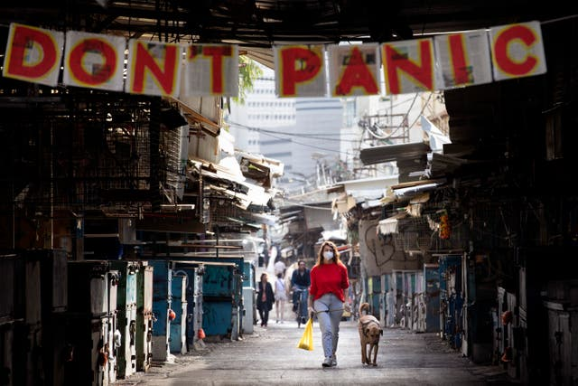 A woman walks her dog under a 'don't panic' sign hanging on the entrance of a food market that was shut down in order to reduce the spread of coronavirus, in Tel Aviv, Israel